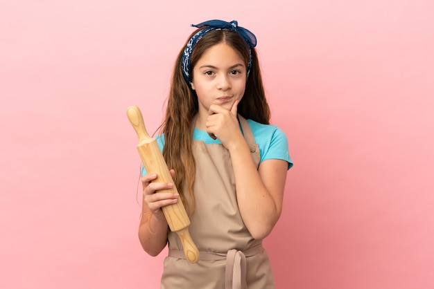 Little caucasian girl holding a rolling pin isolated on pink background thinking