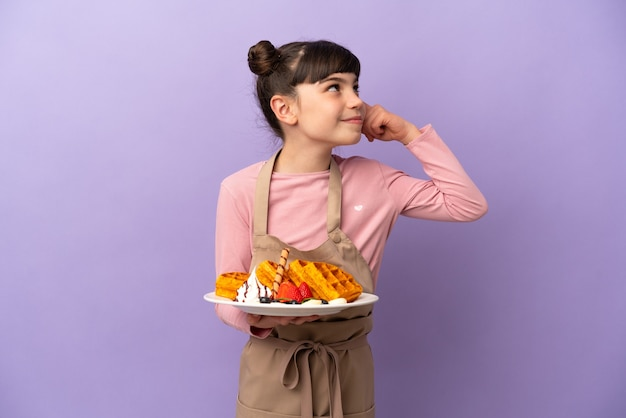 Little caucasian girl holding waffles isolated having doubts and thinking