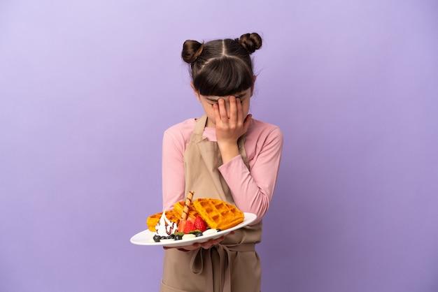 疲れて病気の表情で紫色の背景に分離されたワッフルを保持している小さな白人の女の子