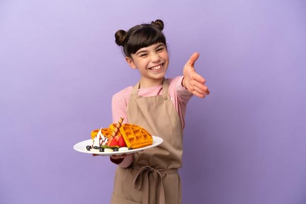 Маленькая кавказская девушка держит вафли, изолированные на фиолетовом, трясет руками за закрытие хорошей сделки