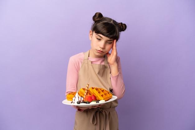 頭痛で紫色の壁に分離されたワッフルを保持している白人の少女