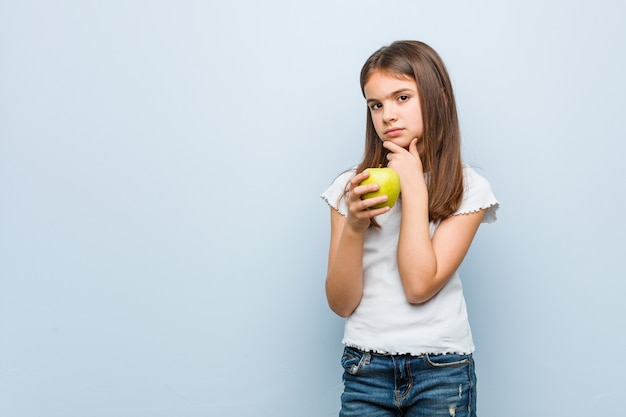 Little caucasian girl holdinggreen apple  sideways with doubtful and skeptical expression.