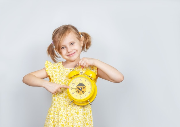 A little caucasian girl holds an alarm clock in her hand and smiles at the camera and points finger at the clock .