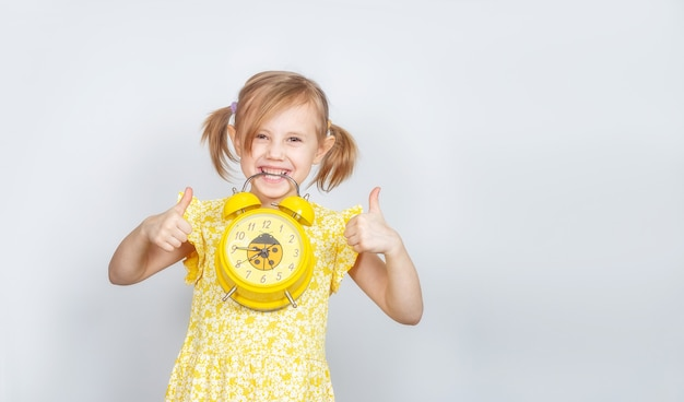 A little caucasian girl holds an alarm clock in her teeth and shows two thumbs up