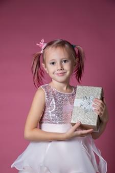 カメラを見てピンクの背景にギフトボックスを保持してポーズスパンコールとお祝いのドレスを着た小さな白人の女の子