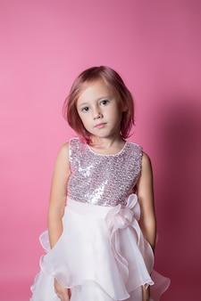 カメラを見てピンクの背景にスパンコールのポーズでお祝いのドレスを着た白人の少女