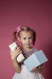 カメラを見てピンクの背景にオープニングギフトボックスをポーズスパンコールとお祝いのドレスを着た小さな白人の女の子