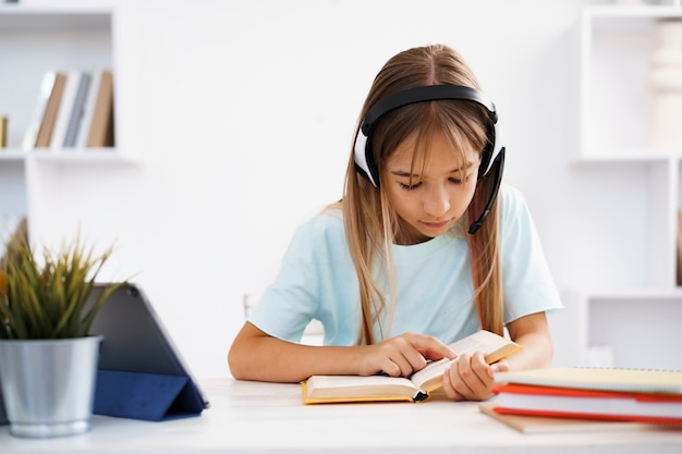 Маленькая кавказская девочка в наушниках имеет видеозвонок в удаленном классе с учителем дома