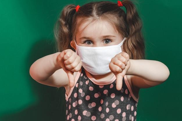 検疫とコロナウイルスパンデミック2020の間に緑の背景に親指のサインを示す医療マスクと水玉模様のドレスを着た白人の少女