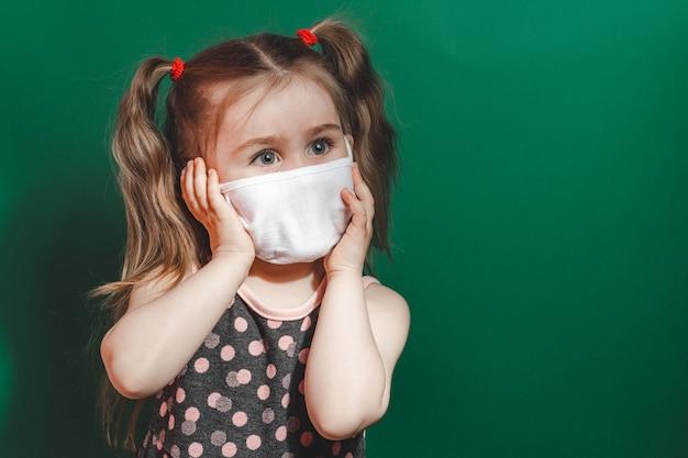 医療マスクの小さな白人の女の子は、緑の背景にスタジオで赤い水玉模様のドレスを着て、痛みで頭を抱えています2021