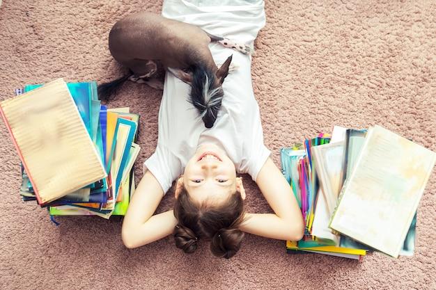 小さな白人の女の子が床で犬と遊んでいます。それらの周りにはたくさんの本があります。女の子は読み込もうとします、犬は彼女に干渉します。