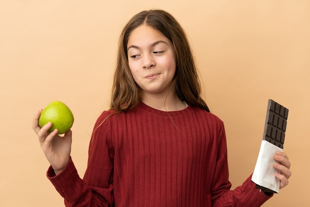 Little caucasian girl isolated on beige background having doubts while taking a chocolate tablet in one hand and an apple in the other