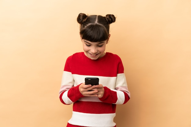 Little caucasian girl isolated on beige background sending a message with the mobile