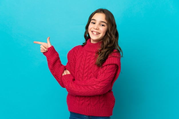 Little caucasian girl isolated on blue wall pointing finger to the side