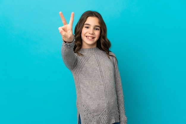Little caucasian girl isolated on blue wall smiling and showing victory sign