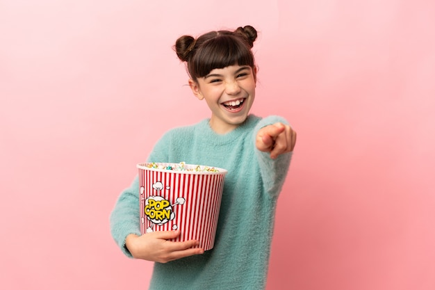 Little caucasian girl isolated holding a big bucket of popcorns while pointing front