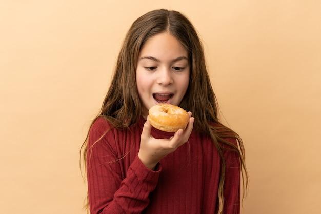 Маленькая кавказская девушка, изолированные на бежевом фоне, ест пончик