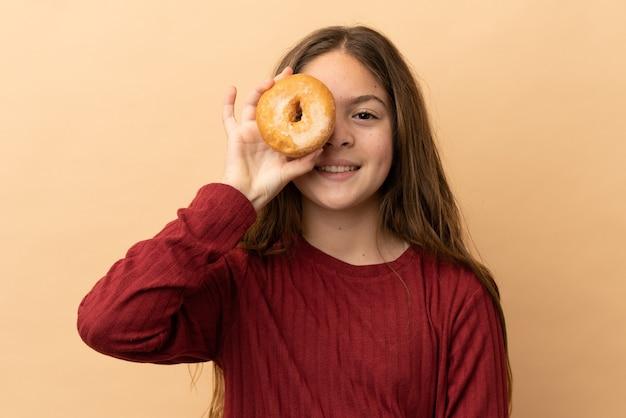 Маленькая кавказская девушка изолирована на бежевом фоне, держа пончик и счастливая