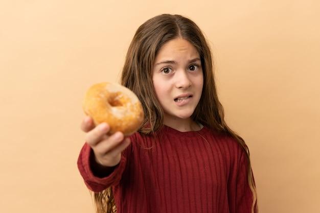 Маленькая кавказская девушка изолирована на бежевом фоне, держа пончик и грустно