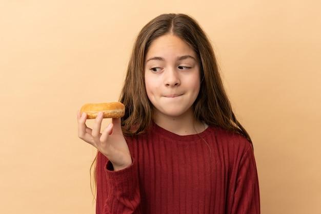 Маленькая кавказская девушка изолирована на бежевом фоне, держа пончик