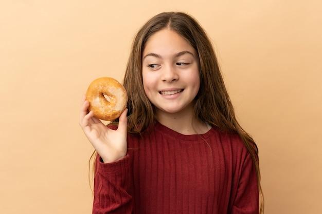 ドーナツを保持し、驚いたベージュの背景に分離された白人の少女