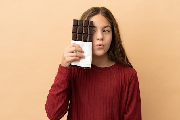 小さな白人の女の子がチョコレートのタブレットを取っているベージュの背景に分離され、驚いた