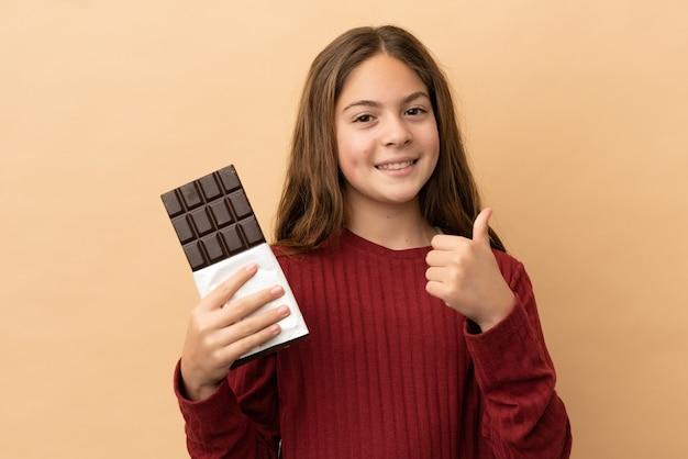 小さな白人の女の子がチョコレートのタブレットを取り、親指を立ててベージュの背景に分離