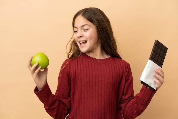 베이지색 배경에 격리된 백인 소녀는 한 손에는 초콜릿 태블릿을, 다른 손에는 사과를 들고