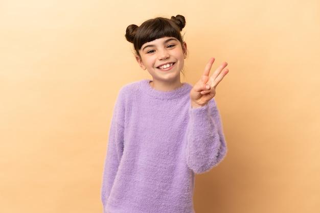 幸せなベージュで隔離され、指で3を数える小さな白人の女の子