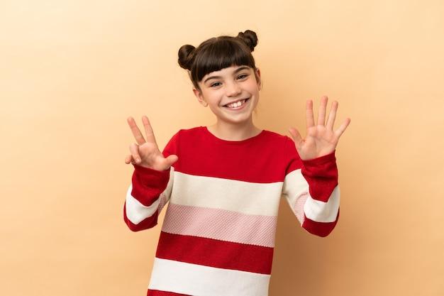 손가락으로 8 세 베이지 색 벽에 고립 된 어린 백인 소녀