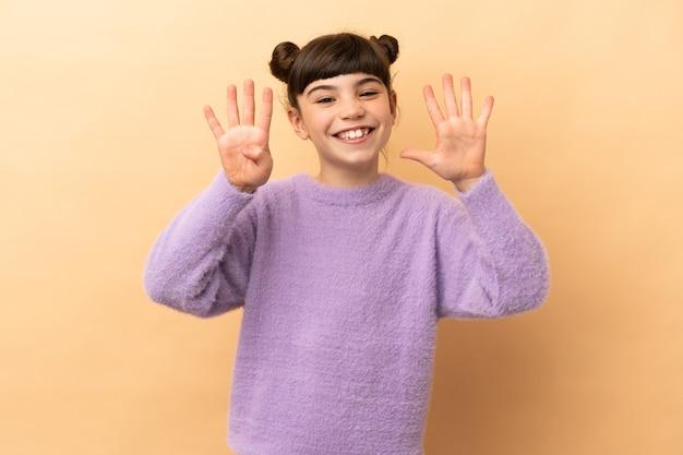 Маленькая кавказская девушка изолирована на бежевой стене, считая девять пальцами