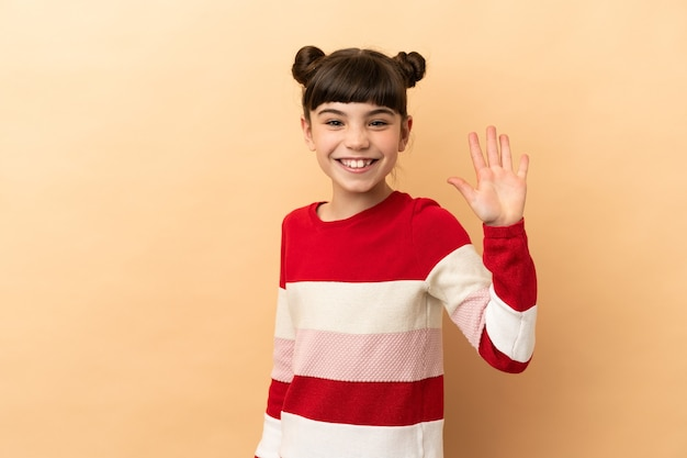 Маленькая кавказская девушка изолирована на бежевой стене, салютуя рукой со счастливым выражением лица