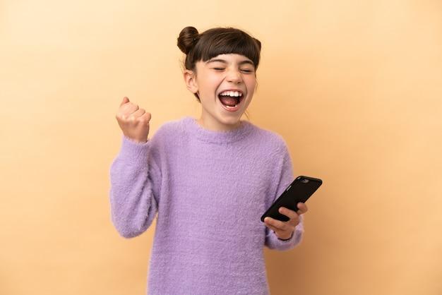 휴대 전화를 사용하고 승리 제스처를하고 베이지 색 벽에 고립 된 어린 백인 소녀