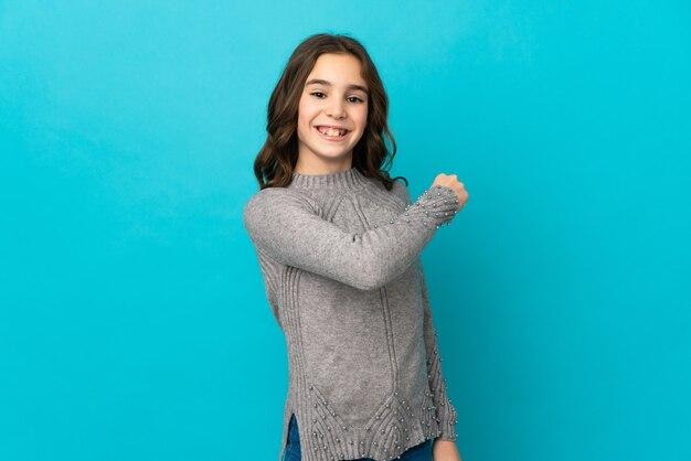 Маленькая кавказская девочка, изолированные на синем фоне, празднует победу