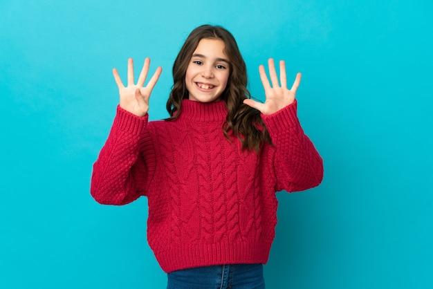 Маленькая кавказская девушка изолирована на синем фоне, считая девять пальцами
