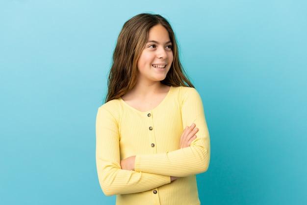 Маленькая кавказская девочка, изолированные на синем фоне, счастлива и улыбается