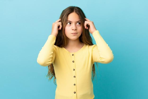 Маленькая кавказская девушка изолирована на синем фоне с сомнениями и мышлением