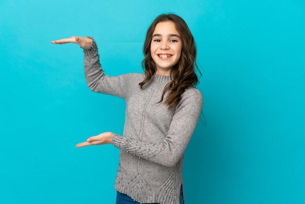 광고를 삽입하는 copyspace 들고 파란색 배경에 고립 된 어린 백인 소녀