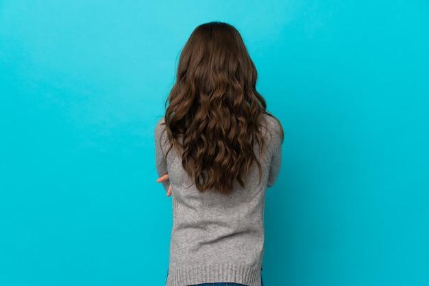 Маленькая кавказская девочка, изолированные на синем фоне в заднем положении