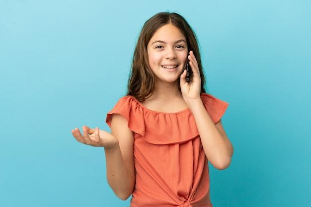 누군가와 휴대 전화로 대화를 유지하는 파란색 배경에 고립 된 어린 백인 소녀