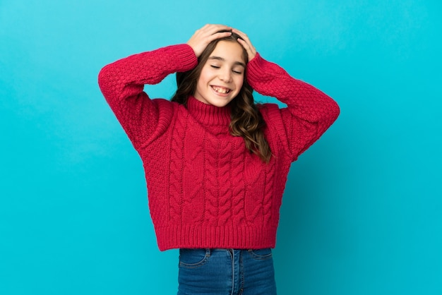 파란색 배경 웃음에 고립 된 어린 백인 소녀