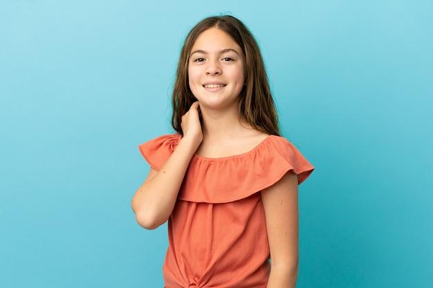 Маленькая кавказская девочка, изолированные на синем фоне смеясь