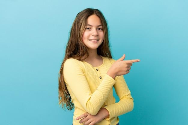 Маленькая кавказская девушка изолирована на синем фоне, указывая пальцем в сторону
