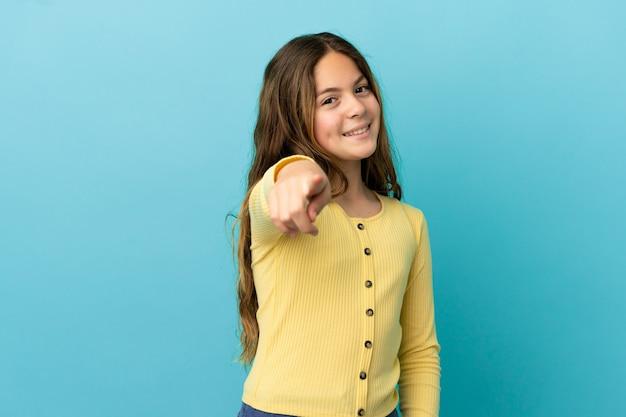 행복 한 표정으로 앞을 가리키는 파란색 배경에 고립 된 어린 백인 소녀
