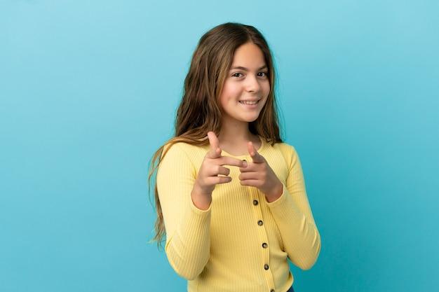 Маленькая кавказская девушка изолирована на синем фоне, указывая вперед и улыбается