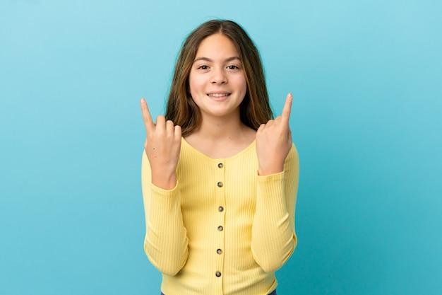 좋은 아이디어를 가리키는 파란색 배경에 고립 된 어린 백인 소녀