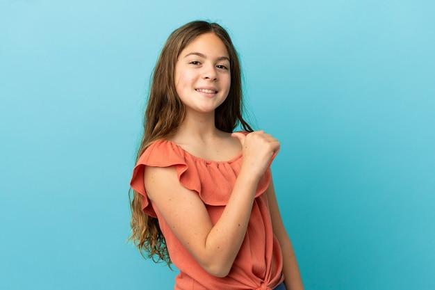 Маленькая кавказская девочка, изолированная на синем фоне, гордая и самодовольная