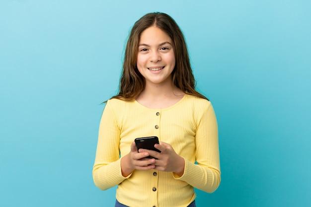 모바일로 메시지를 보내는 파란색 배경에 고립 된 어린 백인 소녀