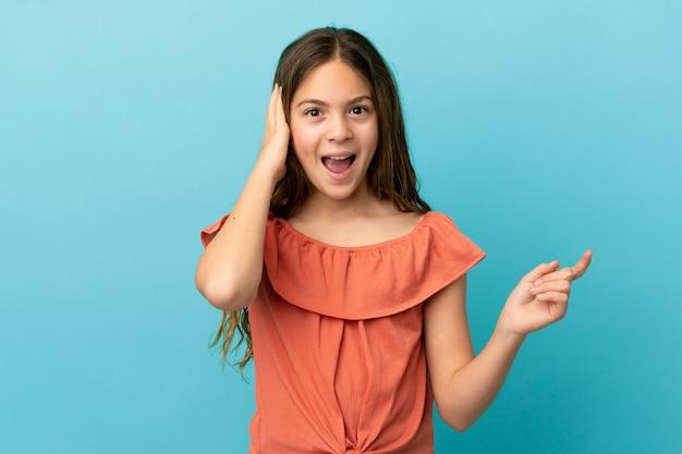 Маленькая кавказская девочка, изолированная на синем фоне, удивлена и показывает пальцем в сторону