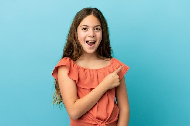 Маленькая кавказская девочка, изолированная на синем фоне, удивлена и указывает сторону
